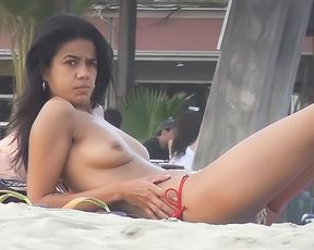 Cutie flaunts her perky mounds in front of a nudist plage voyeur