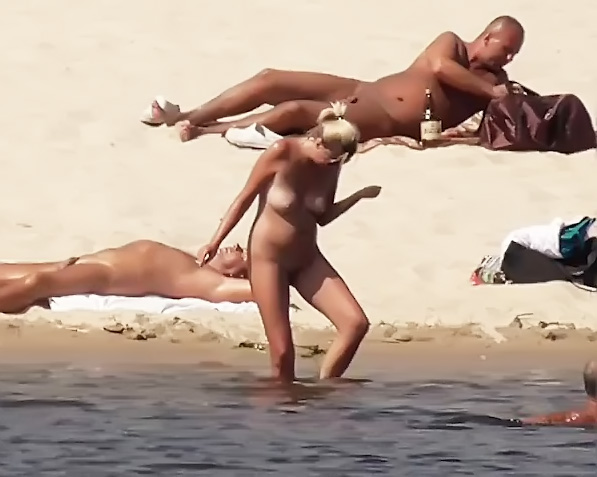 Naked lady naturist lets the water kiss her body